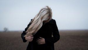 Mulher vestida de preto, grávida, em campo aberto, toma cuidados para preservar a fertilidade