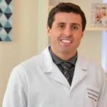 Médico Dr. Rodrigo da Rosa, de jaleco, sorrindo, fala sobre hormônios da gravidez.