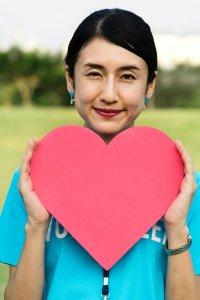 Mulher oriental segura um coração, símbolo do programa de ovodoação