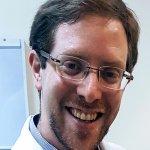 Rosto com óculos, sorrindo, de médico com jaleco branco.