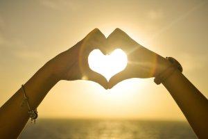 Duas mãos form um coração e ao fudo está o mar e o pôr do sol.
